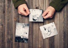 Fotos de família nas mãos do homem e na tabela de madeira resistida parte superior vi Imagens de Stock