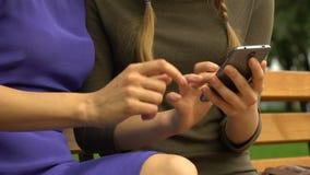Fotos de observação alegres do mum e da menina no dispositivo, usando app em linha interessante video estoque
