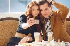 Fotos de observación de los pares jovenes en un teléfono móvil Foto de archivo libre de regalías