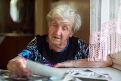 Fotos de observación de la mujer solitaria mayor que se sientan en la tabla imagen de archivo libre de regalías