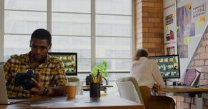 Fotos de repaso masculinas del diseñador gráfico en la cámara digital en el escritorio 4k almacen de video