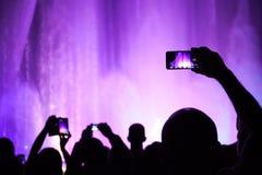 Fotos del lanzamiento de la gente o vídeo de una demostración del concierto o de la iluminación en smartphones Foto de archivo libre de regalías
