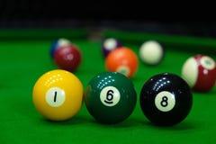 Fotos del primer, jugando las bolas de billar, los diversos números, apuñalando la bola, los números y la tierra verde imagen de archivo