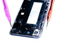 Fotos, die den Prozess der Reparatur eines defekten Handys mit einem Schraubenzieher im Labor f?r Reparatur der mobilen Ausr?stun stockfoto