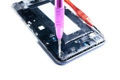 Fotos, die den Prozess der Reparatur eines defekten Handys mit einem Schraubenzieher im Labor f?r Reparatur der mobilen Ausr?stun lizenzfreie stockbilder