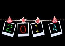 Fotos en blanco del Año Nuevo 2014 que cuelgan en cuerda Imágenes de archivo libres de regalías