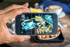 Fotos en la pantalla del smartphone, desayuno simple, cacerolas del huevo, bak Fotografía de archivo