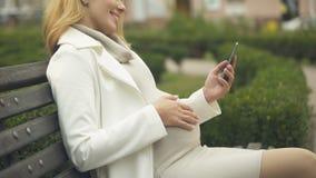 Fotos felizes do smartphone do desdobramento da mulher gravida, relaxando no parque no banco filme