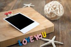 Fotos inmediatas en blanco con los corazones rojos En fondo de madera Foto de archivo libre de regalías