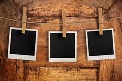 Fotos que cuelgan en el tablero de madera Imagenes de archivo