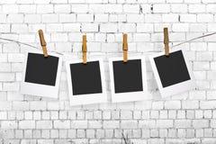 Fotos que cuelgan en una cuerda para tender la ropa en fondo de la pared de ladrillo Fotografía de archivo