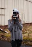 Fotos que hablan del adolescente con una cámara polaroid Foto de archivo libre de regalías