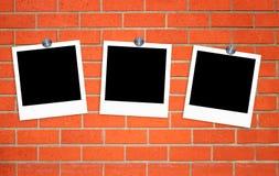Fotos viejas en blanco en los clips en la pared de ladrillo Imagen de archivo