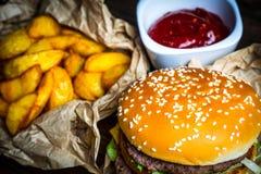 Fotosnabbmat Hamburgare, stekte potatisar och tomatsås royaltyfria bilder