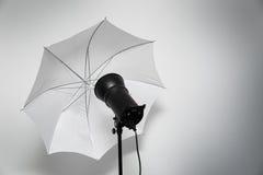 Fotostudioblitz - Röhrenblitzblitz mit weißem Regenschirm Stockbilder