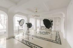 Fotostudioinre klassiska lyxiga lägenheter med en vit spis, en soffa, stora fönster och en ljuskrona Royaltyfria Foton