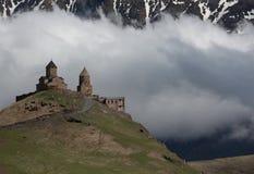 FotoTreenighetkyrka i Gergeti, mot bakgrunden av snöig berg och moln, Georgia Royaltyfri Fotografi