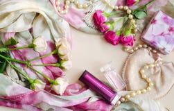 Fototypografie in een zachte uitstekende stijl in pastelkleuren De thee en de roze die rozen liggen op een zijdesjaal, door lipst stock fotografie
