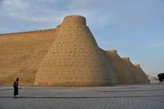 Fotress Ark in Bukhara. Fortress Ark (Uzbekistan) is situated against the blue sky background. Little figure of a tourist (woman) emphasizes strength of the fort Royalty Free Stock Photo