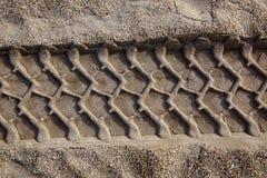 Fotspår för tryck för tilres för bilhjul på strandsanden Arkivbilder