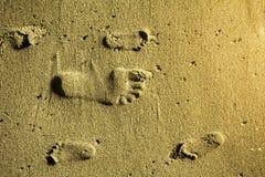 Fotspår i sandvuxen människa och barn arkivfoton