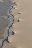 Fotspår i vågorna Arkivfoton
