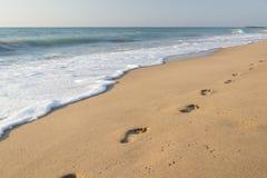 Fotspår på sandstranden Arkivbild