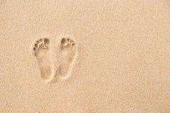 Fotspår på stranden i sandbakgrund arkivfoto