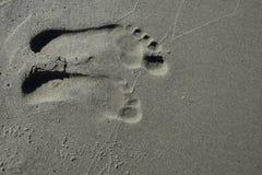 Fotspår på stranden i våt sand arkivfoto
