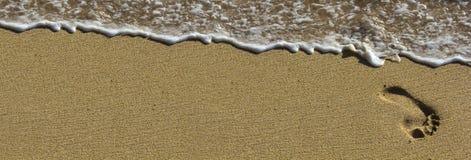 Fotspår på stranden med waves Arkivfoto