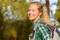 Fotvandra att le för kvinnastående som är lyckligt i kvinnlig fotvandrareflicka för skog Arkivbilder