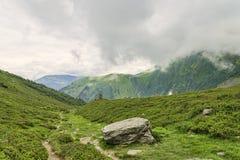 Fotvandra banan bland den gröna alpina dalen Royaltyfri Bild