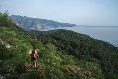 fotvandra berg En flicka står mot bakgrunden av höga berg vila för flicka Arkivfoto