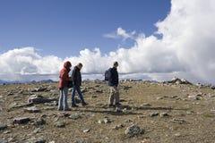 fotvandra bergtoppmöte för familj Royaltyfria Bilder