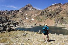Fotvandra i Aosta Valley, Italien Fotvandraren stirrar på den tredje sjön av Lussert fotografering för bildbyråer