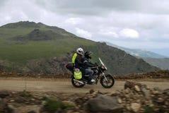 Fotvandra i bergen på en motorcykel royaltyfri fotografi