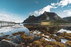 Fotvandra intryck på den Bunes sandstranden med sikt till Bunes Fjorden med trevliga reflexioner på en solig dag med moln på royaltyfria foton