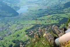 Fotvandra kängor och blommor över en dal Royaltyfria Bilder