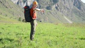 Fotvandra mannen som går på grön bergäng med ryggsäcken Sommarsport och rekreationbegrepp lager videofilmer