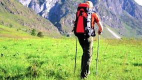 Fotvandra mannen som går på grön bergäng med ryggsäcken Sommarsport och rekreationbegrepp arkivfilmer