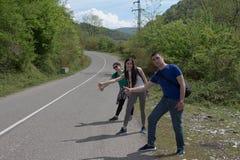 Fotvandra near pinnar mig - lifta Turister i vägauto-stoppet Royaltyfria Bilder
