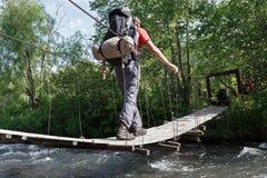 Fotvandra på Kamchatka: turist- korsning bergflod på upphängningbron Royaltyfri Foto