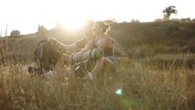 Fotvandra par - fotvandrare som vilar på en kulle Fotvandraresammanträde för ung kvinna och manpå jordtyckande om le för sikt som stock video
