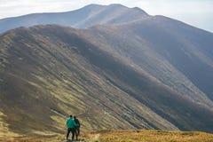 Fotvandra par, klättraren eller slingalöparen i berg, inspirerande landskap Motiverade fotvandrare som ser bergsikt Arkivbild