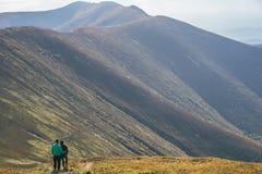 Fotvandra par, klättraren eller slingalöparen i berg, inspirerande landskap Motiverade fotvandrare som ser bergsikt Royaltyfri Bild