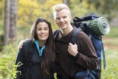 Fotvandra par med ryggsäckar i skog Arkivfoto