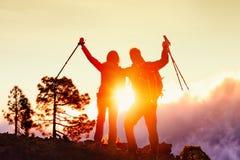 Fotvandra par som är lyckliga vid bergsolnedgång i framgång Arkivbilder