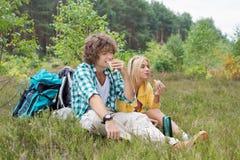 Fotvandra par som äter smörgåsar, medan koppla av i fält Arkivbild