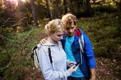 Fotvandra par som kontrollerar kompasset Arkivfoto