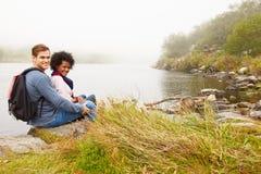 Fotvandra par som kopplar av av kanten av en sjö som ser till kameran Arkivfoto